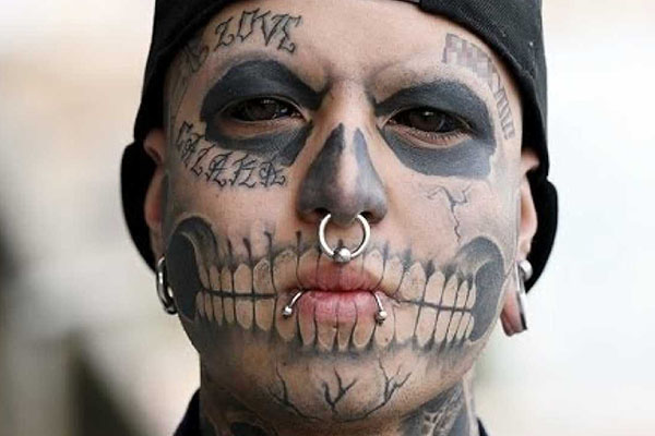 A person with facial tattoos and piercings