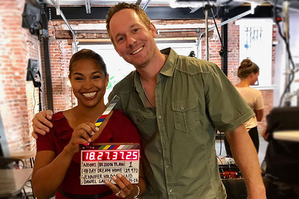 A man and a woman smiling with a clapperboard