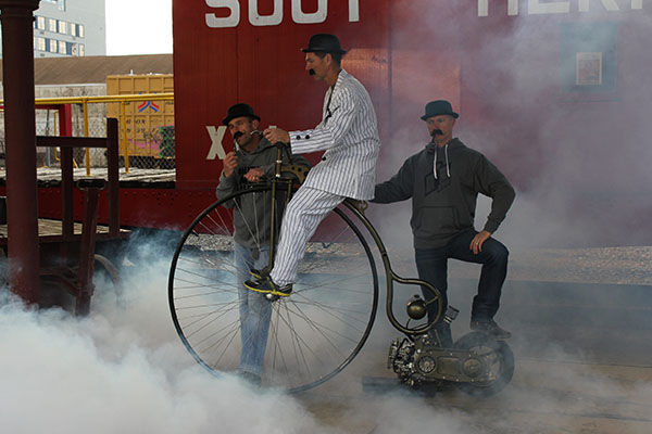 Three men on an old-style bicycle