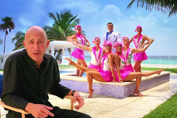 A man in front of synchronized swimmers